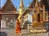 Stock Video Footage of A Buddhist monk in orange robes walks out of a Buddhist temple with a golden