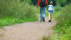 Father with son walking in park, join hands, from camera Stock Footage