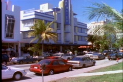 Pedestrians and car traffic pass by an art-deco building in Miami Beach, Stock Footage