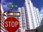 A stop sign, one way sign and a street sign stands in front of an art deco Stock Footage