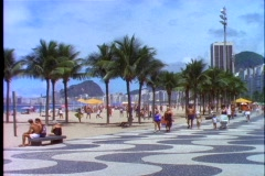 Stock Video Footage of Pedestrians walk down the walkway of Copacabana beach in Rio De Janeiro, Brazil.