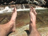 Stock Video Footage of POV shot of a man's feet relaxing beside a small waterfall.