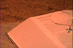A gold cross rests cross a Bible over the book of John. Stock Footage