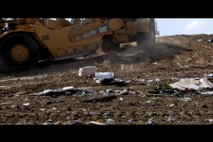 A large machinery moves through a garbage dump. Stock Footage