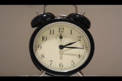 Close-up of an alarm clock's hands, quickly moving around its face. Stock Footage