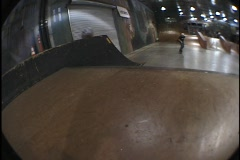 A skate-boarder makes a jump at an indoor skate park. Stock Footage