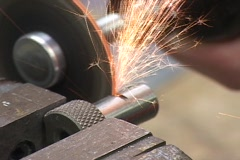 A saw cuts a large metal bolt. Stock Footage