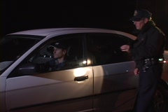 A police officer walks up to a car that he has pulled over and Stock Footage