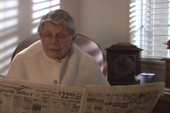 An older woman reads the newspaper as her coffee cup emits steam. Stock Footage