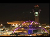 Stock Video Footage of Airplanes fly past an airport control tower at night.