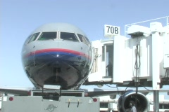 A passenger loading dock pulls away from a jet. Stock Footage