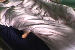 A woman sleeps wrapped in a comforter with her foot dangling outside the covers. Stock Footage