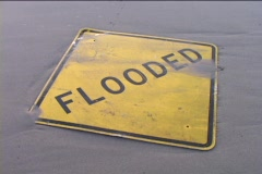 A street-sign that reads FLOODED is covered in mud as waves come in and go out. Stock Footage