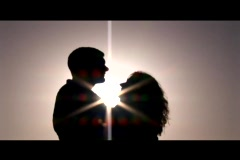 Medium shot of a couple embracing and kissing silhouetted against the sun. Stock Footage