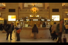 People purchase tickets, and mill around a train stations ticket booth in this Stock Footage