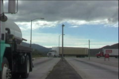 Semi trucks rush through a weigh station along the highway. Stock Footage