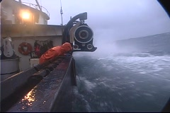A lobster fishermen throws a rope out and catches a buoy in treacherous Stock Footage
