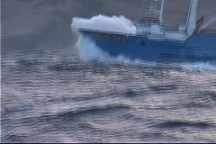A crabber vessel breaks through the large waves of the Bering Sea. Stock Footage