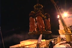 Following-pan of crab fishermen holding onto a cage as they are moved across the Stock Footage