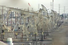 Medium shot of oil derricks pumping in a large oil field. Stock Footage