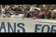 Pan-left shot of anti-Iraq-war protestors marching in Washington DC carrying a Stock Footage