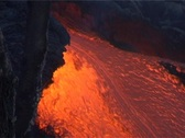 Stock Video Footage of Red hot lava flows down the slopes of a volcano.