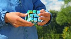 Boy solves earth cube in park, close-up hands Stock Footage