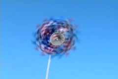 A red white and blue patriotic pinwheel spins in the wind against Stock Footage