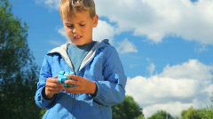 Boy solves earth cube in park Stock Footage