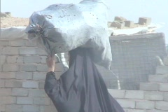 A veiled Muslim woman walks down a street in rural Iraq carrying Stock Footage