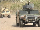 Stock Video Footage of US Army armored Humvees head down a road in Iraq.