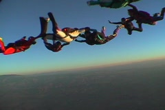 Nine skydivers maneuver in formation and disperse. Stock Footage