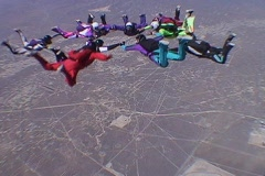 Ten skydivers free fall in a circle and disperse. - stock footage