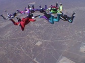 Stock Video Footage of Ten skydivers free fall in a circle and disperse.