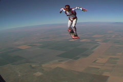 A skydiver performs skyboarding maneuvers. Stock Footage