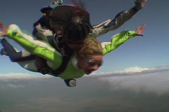 Tandem skydivers free fall and deploy their parachute. Stock Footage