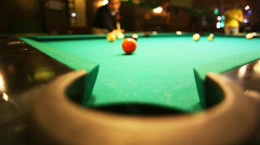 man in billiards shoots orange ball in pocket - stock footage