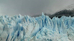 The spiked tops of a glacier stand against rugged mountains. Stock Footage
