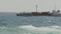 Waves roll into a rocky shore with a freighter ship in the Stock Footage