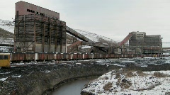 An abandoned mine with ore rail cars in the foreground. Stock Footage
