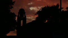 An old California style mission bell tower against a sunset sky. Stock Footage