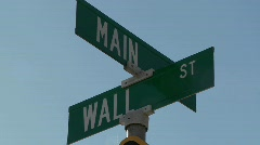 A street sign indicates the intersection of Main and Wall Streets. - stock footage