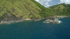 Aerial flight along rocky ocean cliff with forest Stock Footage