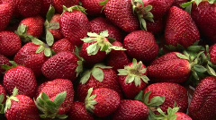 Red strawberries sit in a pile on a surface. - stock footage