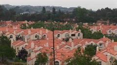 Thick vegetation surrounds a neighborhood of stucco homes. - stock footage