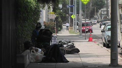 Homeless men sit on a sidewalk. Stock Footage