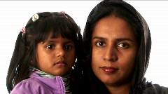 A woman wears a headscarf and lipstick while holding a young girl. Stock Footage