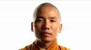 A Buddhist monk wearing an orange robe. Stock Footage