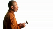 A Buddhist monk wearing an orange robe taps a bell with a Stock Footage