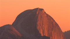 The golden-hour sun glows over a mountainous landscape in Stock Footage